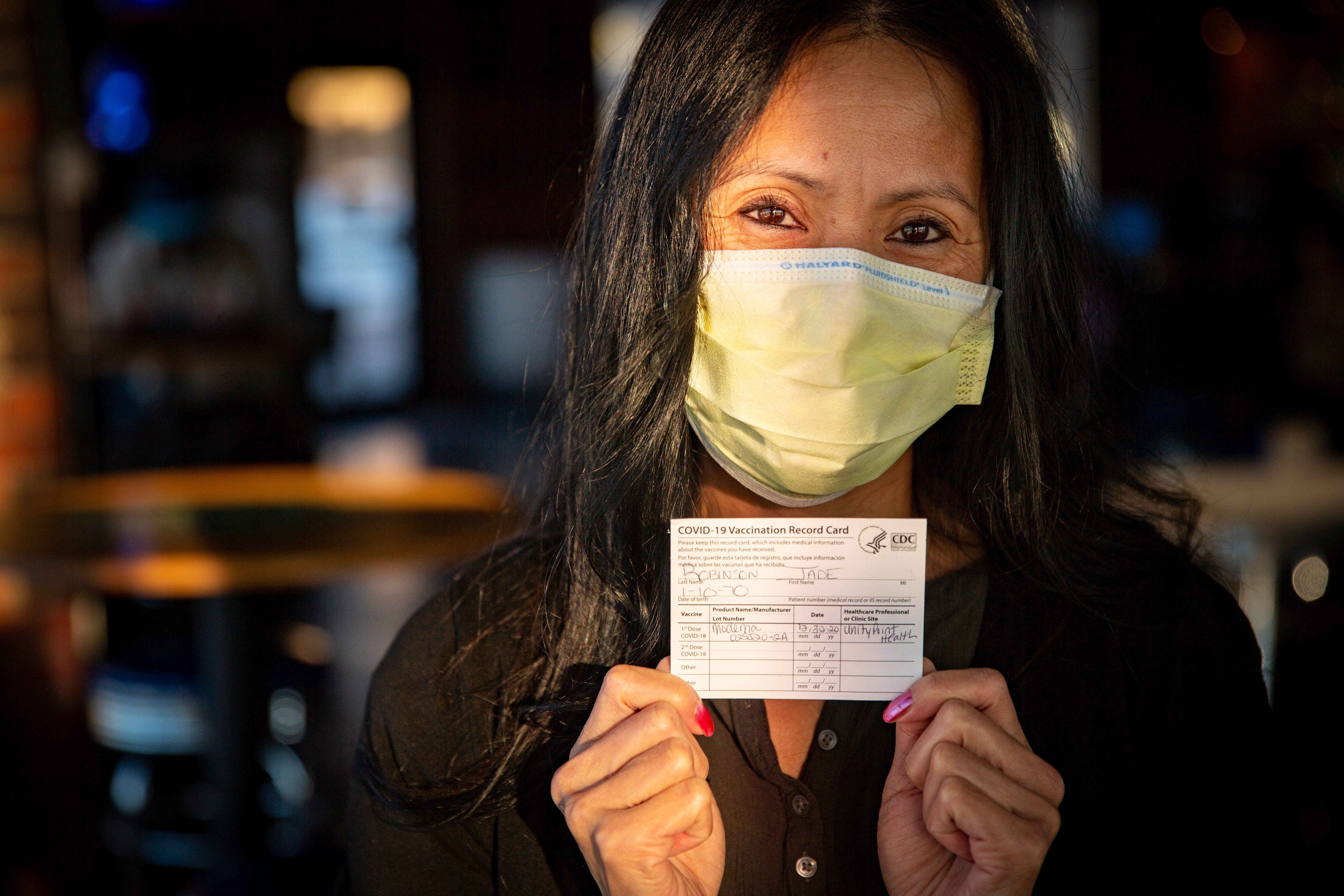 Jade Robinson holds her COVID-19 vaccination record in Des Moines on Jan. 27.