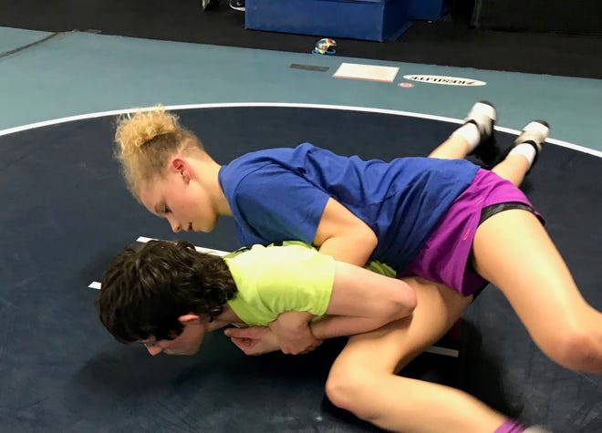 Great Falls High freshmen Kaylin Taylor, in blue, and practice partner Cash Clark work on a wrestling drill during practice in the wrestling room at the Old Bison Gym.
