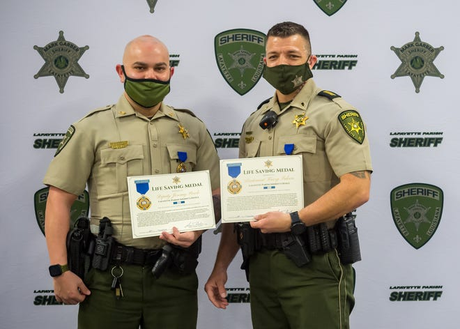 Sheriff Mark Garber presents Lafayette Parish Sheriff's Deputy Jeremy Percle (L) and Lieutenant Karry Falcon (R) with Life Saving Medals for their life-preserving actions while on duty. Thursday, Jan. 28, 2021.