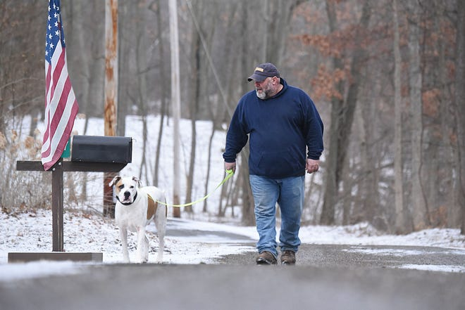 Jeff Lewis walks his dog Leon Thursday morning near Charles Mill Lake.The dog was rescued by members of the Mifflin Fire Department after falling through the ice over the weekend.
