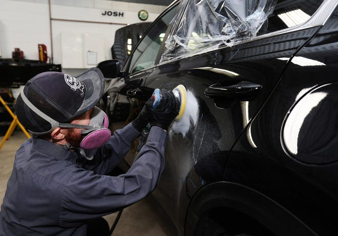 Josh Annis, collision repair technician at Prestige Auto Repair on Wednesday, Jan. 27, 2021, sands out damages on the left rear passenger door of a Kia that was brought in for repairs after it was stolen. The window was broken on the door during the theft.