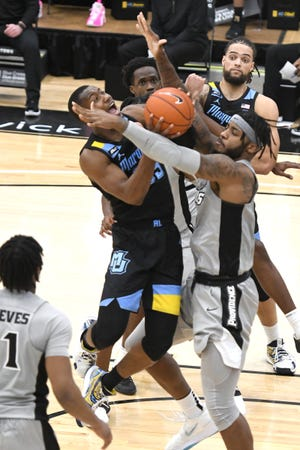 Marquette guard Koby McEwen tries to put up a shot against the defense of Providence center Nate Watson.