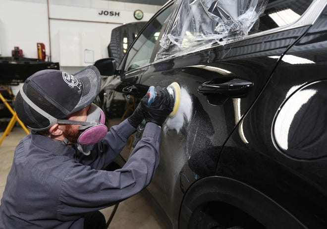 Josh Annis, collision repair technician at Prestige Auto Works, on Wednesday sands out damages on the left rear passenger door of a Kia that was brought in for repairs after it was stolen. Kia models seem to be among the more popular cars for teen auto thieves, and Prestige Auto Repair is seeing an increase in Kias coming in for repairs.