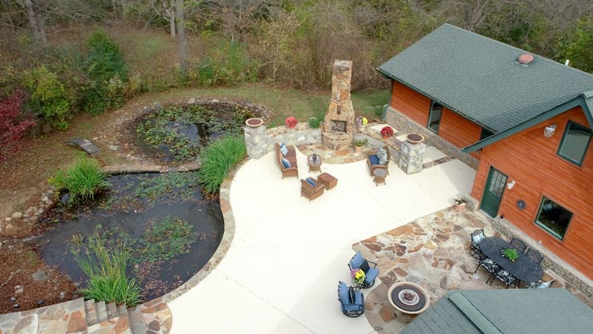 This drone view shows the pond and the outdoor patio fireplace.