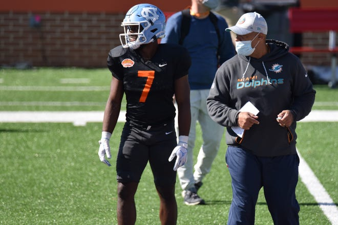Former Navarre and University of North Carolina running back Michael Carter stands with a Miami Dolphins coach (right) during Senior Bowl practice on Jan. 28, 2021 at Hancock Whitney Stadium in Mobile, Alabama.