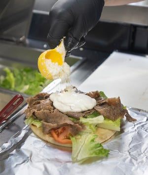 Shelby Arnold tops off a gyro Jan. 27 at Greek's Catering and Events food truck on Spanish Trail in Pensacola.