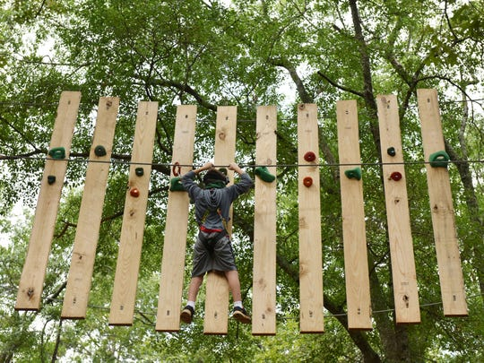 Luke Smith, 9 walks through a ropes course at Treetop Quest in Greenville.