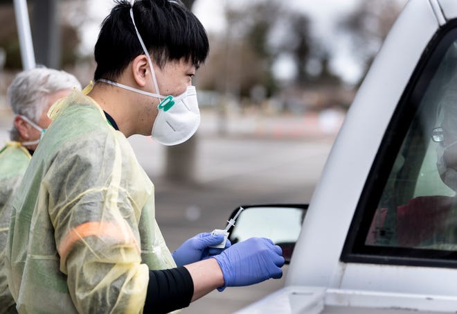 Student nurse Yahxi Zhang, prepares to give a COVID-19 vaccine injection during the drive-thru event at College of the Sequoias on Friday, January 22, 2021.