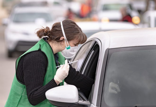 Student nurse Erica Hendrick prepares to give a COVID-19 vaccine injection during the drive-thru event at College of the Sequoias on Friday, January 22, 2021.