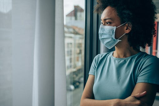 A Black woman wearing a mask looks through a window during the coronavirus pandemic.