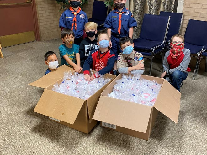 Boy Scout Pack 343, Pack 13 Tiger Den, and Troop 34 volunteered to package Valentine's Day bags for Meals on Wheels clients.  Standing are Carter Webb, left, and Christopher Van Pelt.