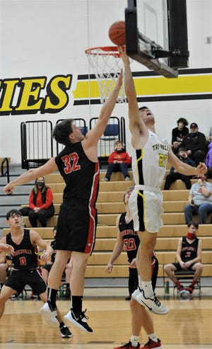 Tri-Valley's Aaron Frueh lays the ball in against Crooksville's Thomas Russell in Wednesday's MVL contest. The Scotties won 76-51.