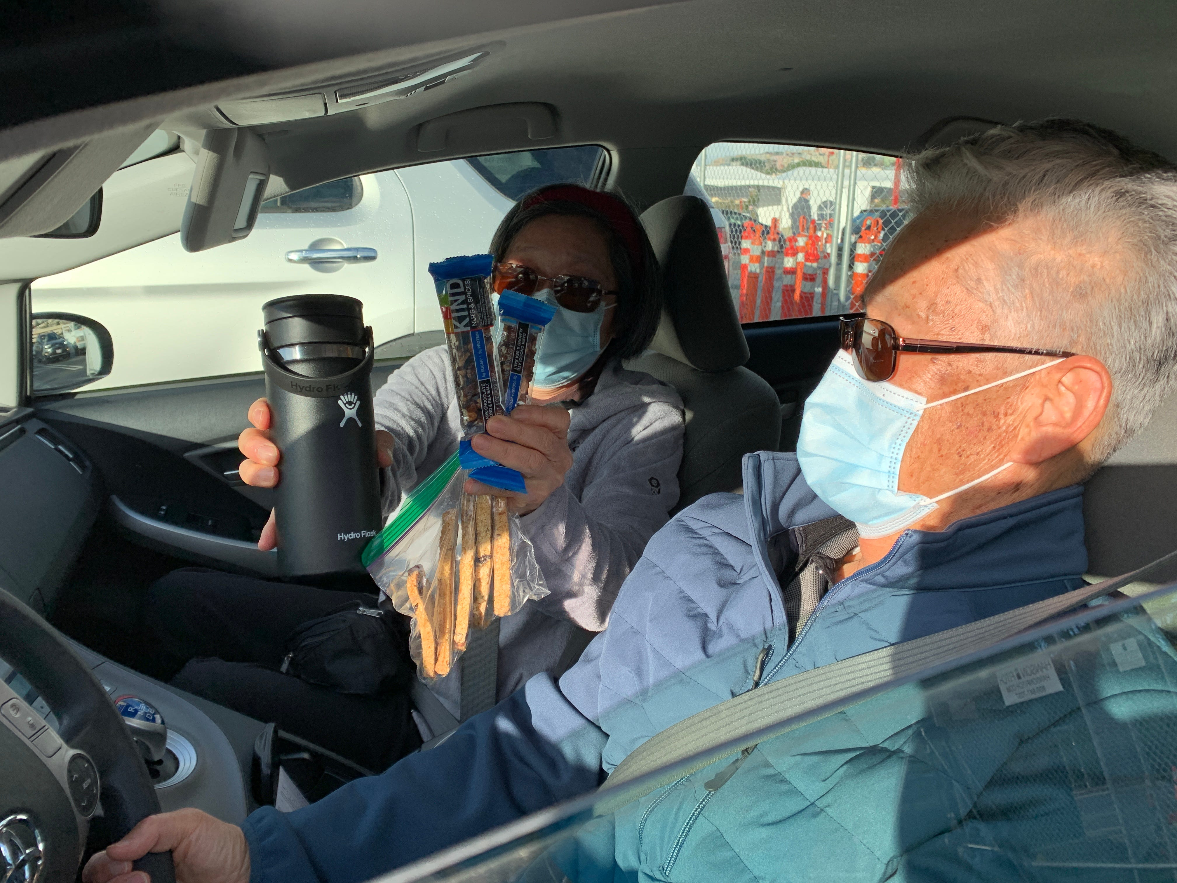 Inja Kim, 72, shows the snacks she brought in expectation of a long wait to get the COVID-19 vaccine for her husband Kwang Kim seated next to her. The couple made it through San Francisco's mass vaccination clinic on January 22, 2021 in just 25 minutes.