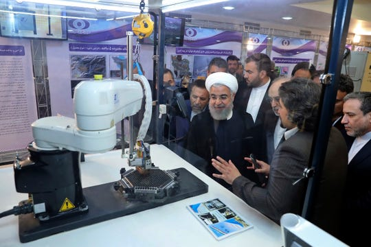 In this April 9, 2018, Iran's President Hassan Rouhani listens to explanations on new nuclear achievements at a ceremony to mark 'National Nuclear Day,' in Iran.