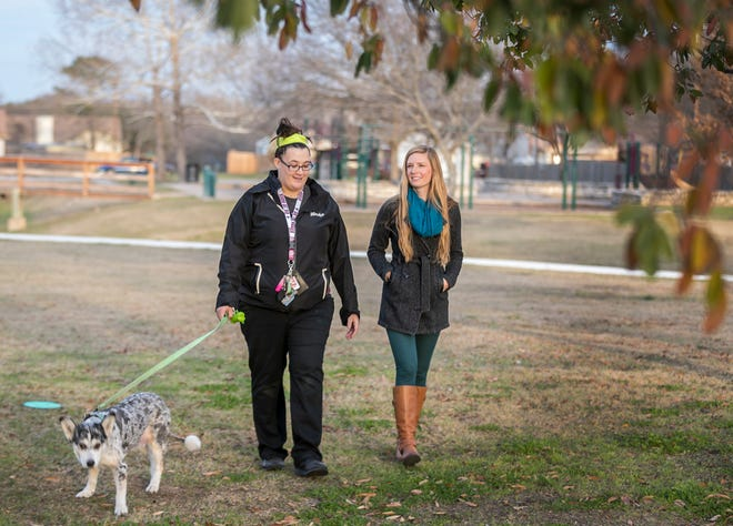 Mandy Donaldson, left, a former foster child, walks with her mentor Dana Narveson and her dog Bailey in Round Rock's Frontier Park last week. Donaldson has been able to get her on her feet financially and climb out of a large deficit. The 22-year-old is now able to pay bills on time and is saving for her wedding.