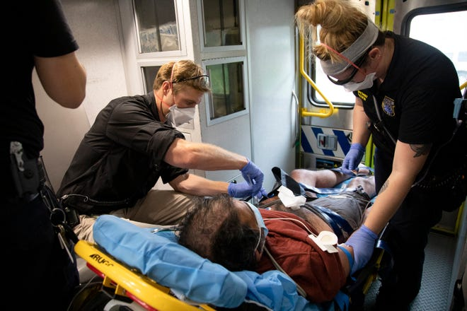 In this 2020 file photo, a paramedic practitioner gives a man medication as Austin-Travis County EMS medics assist.