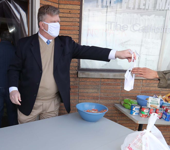 Munroe Falls Mayor James Armstrong hands a mask to a man who has arrived to receive a meal at Peter Maurin Center last month in Akron. Cuyahoga Falls, Stow, Munroe Falls and Silver Lake held friendly competition to see which would donate the most winter supplies to the center.