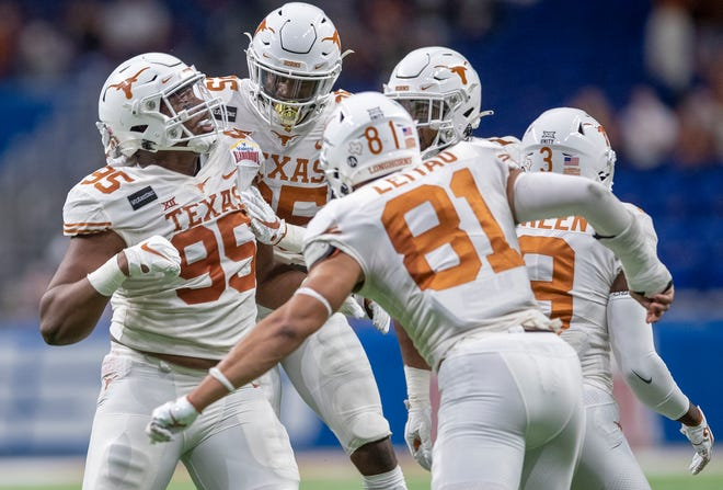 Texas defensive lineman Alfred Collins, left, celebrates his interception against Colorado during last season's Alamo Bowl victory at the Alamodome. The Longhorns will open their 2021 season Sept. 4 at home against Louisiana.