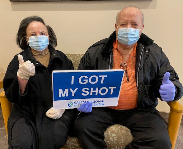 Dr. Anthony Rich, right, and his wife, MaryAnn, show off a sign signaling that they received a dose of the COVID-19 vaccine Thursday at Salem Regional Medical Center.