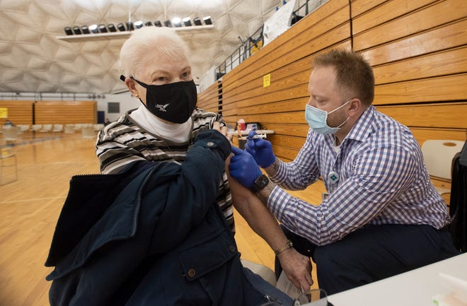 Heritage Valley Health System registered nurse Rody Schwartzel administers a COVID-19 vaccine to Donna Rhodes, 82, of Baden, Thursday at the CCBC Dome in Center Township. [Sally Maxson/For BCT]