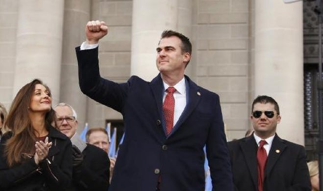 Gov. Kevin Stitt acknowledges applause from the crowd on Jan. 14, 2019, after taking the oath of office. At left is his wife, Sarah. Behind her are former Gov. Brad Henry and his wife, Kim.