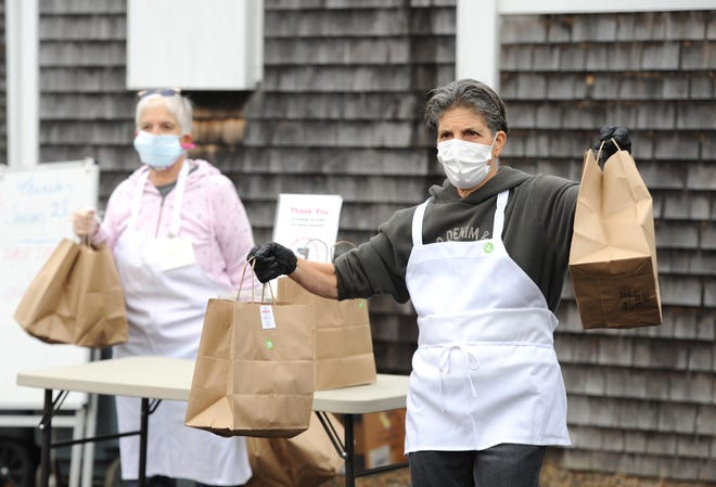 Volunteers Lorraine DeProspo, right, and Gerri Spinella, both of Provincetown, hold bagged lunches of Bulgarian-inspired food waiting to be handed out Thursday at the Soup Kitchen in Provincetown. The newly established drive-thru operation is at the United Methodist Church.