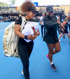 Naomi Osaka, left, and Serena Williams walk from the court together following an exhibition event in Adelaide, Australia, on Friday.