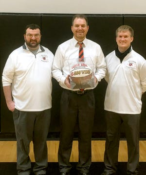 Tim Cool, center, in his 10th year as head coach of the Chillicothe High School basketball Hornets poses with a ceremonial basketball denoting the 500th victory of his high school coaching career Thursday after the Hornets defeated Kansas City: Northeast 54-48 in the Cameron Invitational Tournament consolation semifinals. Flanked by Tim Cunningham (left), his chief assistant coach throughout Cool's CHS tenure, and another veteran assistant, Canaan Fairley, who also helped generate a healthy percentage of those 500 victories while a player under Cool at Newtown-Harris, the presentation was made following Thursday's victory by Dan Nagel, CHS director of athletics and principal.