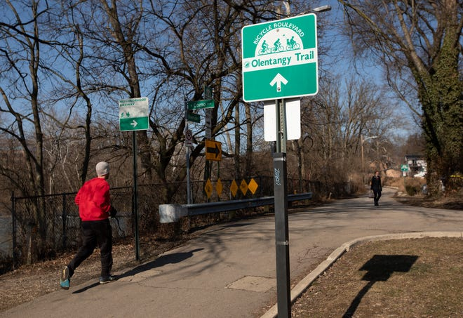 Joggers and walkers use the Olentangy Trail near Clinton-Como Park in Clintonville, where a proposed bridge over the Olentangy River could alter the trail.