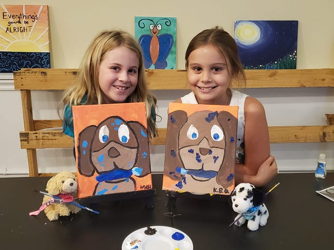 Kylie Quinlan and Mila Beranek show off their art class projects at Something New.