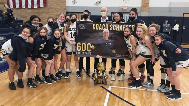 William Chrisman girls basketball coach Scott Schaefer, center, poses with his team after it defeated crosstown rival Truman 65-35 Thursday to give him his 600th career win. The team earned the Three Trails Trophy, front, and Schaefer was presented with a commemorative banner to mark his milestone win.