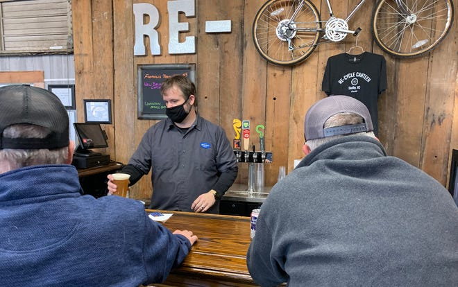 Scott Moss serves craft beers to customers at Re-Cycle Canteen inside of Bicycles of Shelby. [Diane Turbyfill/The Star]