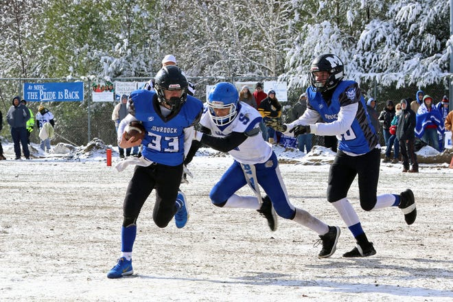 Murdock quarterback Jack Polcari (33) runs away from Narragansett's Antonio Brea during the Blue Devils' and Warriors' annual Thanksgiving Day clash at snow-covered Alumni Field in Winchendon in 2018. The MIAA on Friday approved safety modifications for football and other fall sports that will now begin during the late-winter chill of February due to the COVID-19 pandemic.