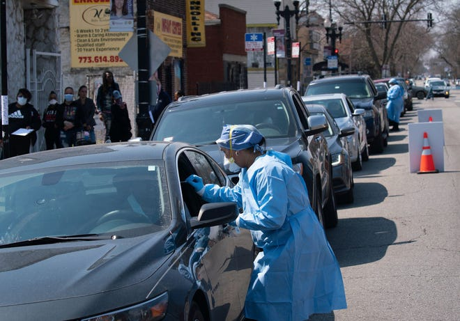 People wait in line in their cars to get tested for COVID-19 at Roseland Community Hospital on April 3, 2020 in Chicago, Ill.