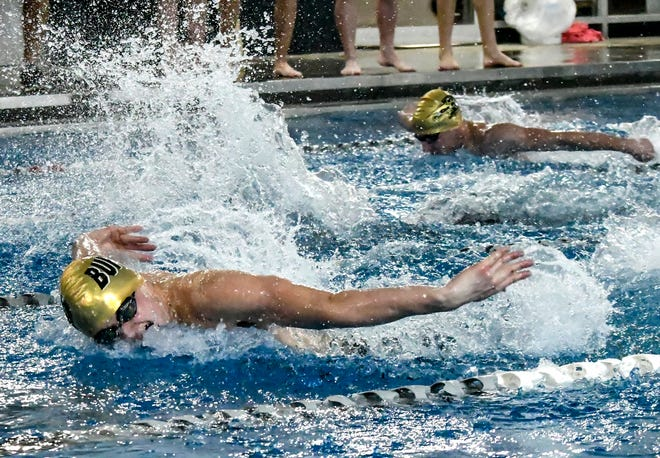 Garden City High School's Connor Cupp, left, and Kobe Otero both come up for a breath and make strokes Thursday while competing in the 100 butterfly during a home swimming dual at the Garden City Family YMCA. Cupp claimed two state qualifying times in events at the meet.