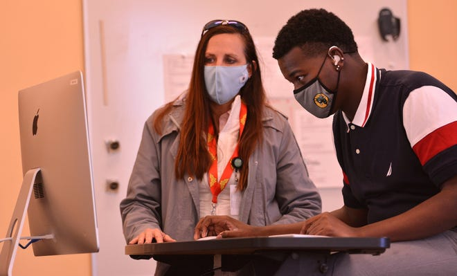 Students in Iosep MacDougall's Digital Arts class work on a project at the South Carolina School for the Deaf and the Blind, in Spartanburg, Thursday, January 28, 2021. Cherie Winkler, principal of the Applied Academic Center, helps Tyrelle Stevenson, right, during the class.