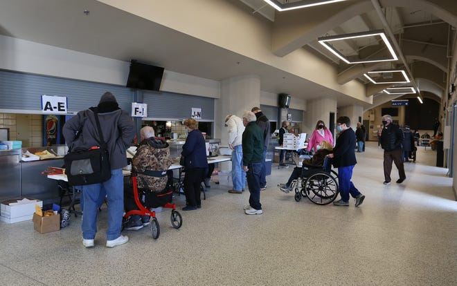 People check in at the registration tables as they come in for their COVID-19 vaccination during the Reno County Vaccination Distribution event at the Sports Arena.