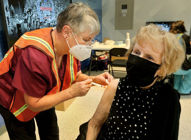Julie Teeter receives her COVID-19 vaccination from Jane McLaughlin, a registered nurse, during the Reno County Vaccination Distribution event held at the Sports Arena on Friday. Vaccines were given to 700 people on Friday.