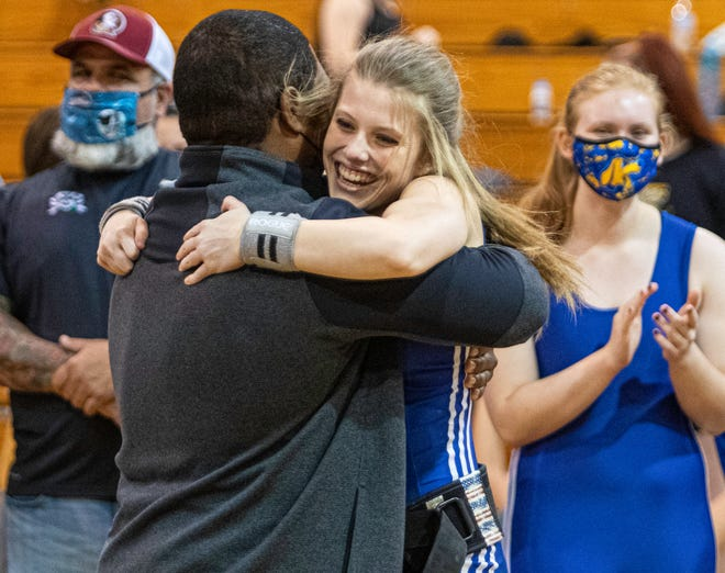 Auburndale senior Emily Hart hugs head coach Gilbert Jones after setting the state record of lifting 185 pounds in the clean-and-jerk in the 119-pound division on Thursday in the Class 2A, Region 3 girls weightlifting meet at River Ridge High School.