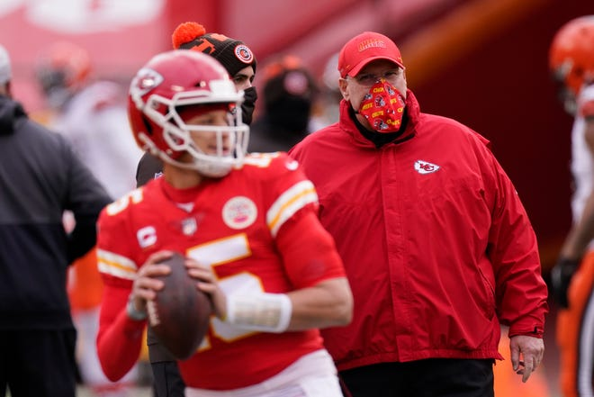 FILE - In this Sunday, Jan. 17, 2021 file photo, Kansas City Chiefs head coach Andy Reid, right, watches quarterback Patrick Mahomes warm up before an NFL divisional round football game against the Cleveland Browns in Kansas City.