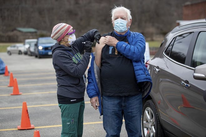 Joe Beasley of Barboursville, right, receives a COVID-19 vaccine from Marshall University student nurse Angie Bush, left, as health care workers with the Cabell County EMS and Cabell-Huntington Health Department administer vaccines during a drive-thru clinic on Thursday, Jan. 21, 2021, outside of the St. Mary's School of Nursing in Huntington, WVa.
