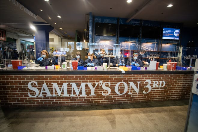 Instead of serving up drinks at Sammy's on 3rd, a team prepares COVID-19 vaccinations before they are administered.