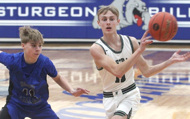 Westran High School junior Trey Marble makes a 'no-look' pass while being defended by South Callaway's Tayber Gray during Thursday's semifinal game of the Sturgeon Invitational. Marble supplied three 3-pointers and 11 points to help the top-seed Hornets win 67-49.