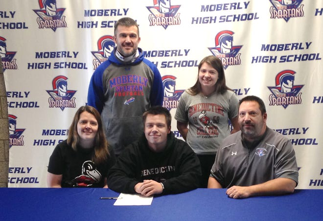 Moberly High School senior Dominic Stoneking sits between his parents, Tricia and Tony, during a letter of intent signing ceremony held Thursday, Jan. 28. Stoneking accepted a football scholarship offer fo the 2021-22 academic year at Benedictine College in Atchinson, Kan. Standing are Spartans head football coach Cody McDowell and Dominic's older sister, Isabella.
