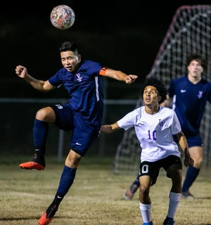 Vanguard's Dayron Bonilla heads the ball above Lake Weir's Kenneth Hoare. The Knights defeated the Hurricanes, 4-2, Thursday night.