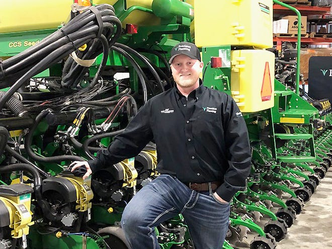 Casey Hettinger stands next to a planter on his Champaign County farm last week.
