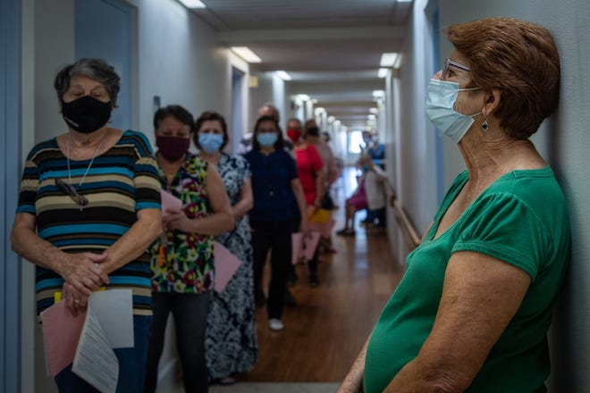 Residents and staff wait to be inoculated with Pfizer-made COVID-19 vaccine at AHEPA 18 Senior Apartments in West Palm Beach, on Jan. 13.