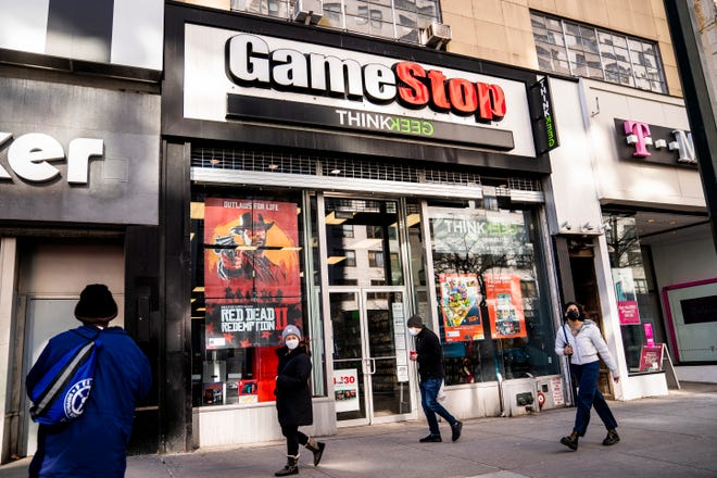 Pedestrians pass a GameStop store on 14th Street at Union Square, Thursday, Jan. 28, 2021, in Manhattan. Robinhood and other online trading platforms are moving to restrict trading in GameStop and other stocks that have soared recently due to rabid buying by smaller investors defying short sales by hedge funds.