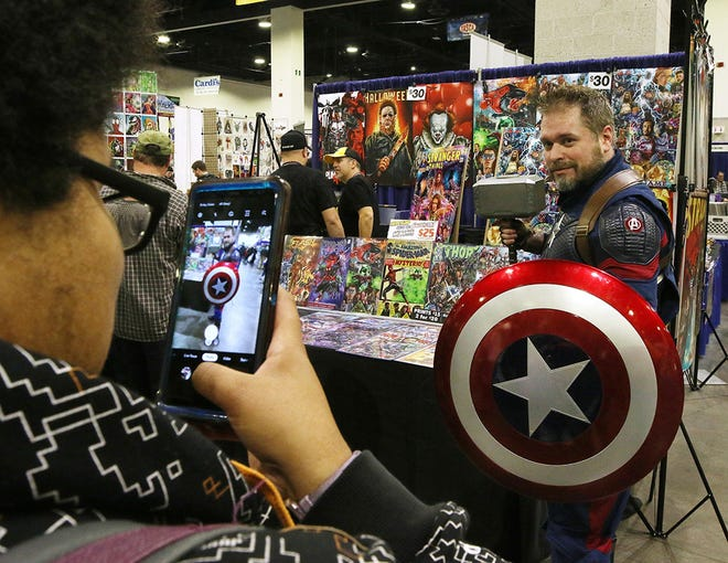 Brian Holdsworth of Weymouth, Massachusetts, dressed as Captain America, poses for a photo at the November 2019 Rhode Island Comic Con. Many such shows are in limbo amid the ongoing pandemic.