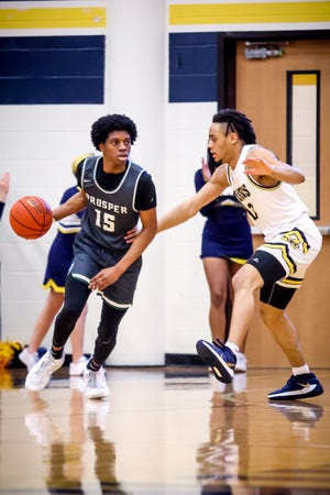Prosper's Justin Olaleye (15) drives past Devin Vincent (13) during a game against McKinney  High on Friday, Jan. 22, 2021. McKinney High won the game 79-46.